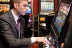 Young men gambling in the casino on slot machines