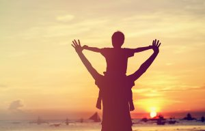 father holding son in front of sunset