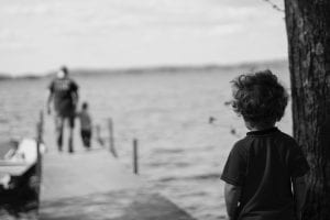 Child looking down pier