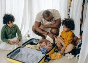 father packing suitcase with children